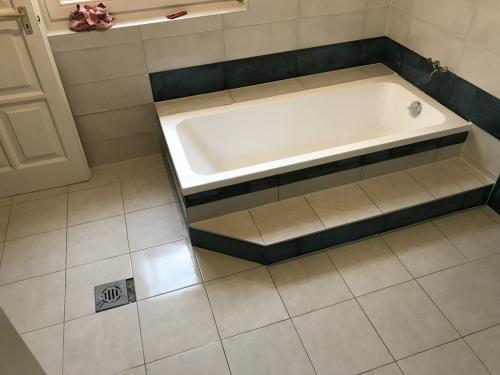 Elkészült fürdőszoba: ezüstszürke és türkiz színű fugákkal
